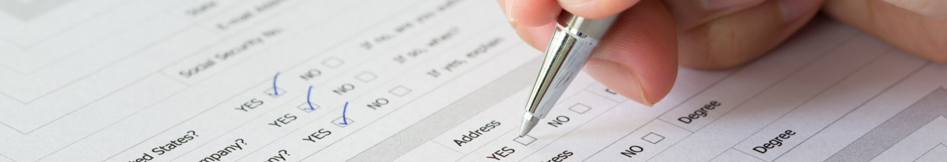 hand with pen over blank check boxes in an application form